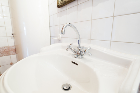 detail of faucet and white sink