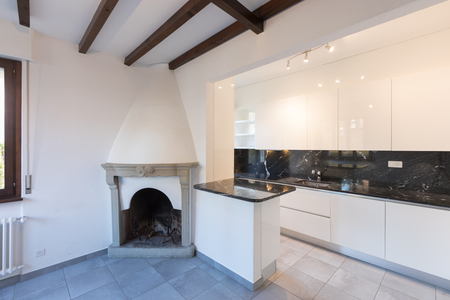 Interior of new modern kitchen in open space with fireplace