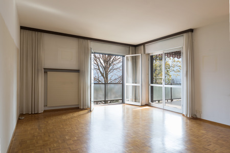 Flat living room to be restored with a view of the Ticino hills. Nobody inside Banco de Imagens