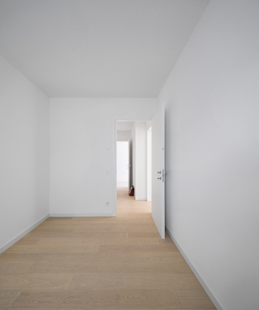 Front view of a white room with parquet. Nobody inside