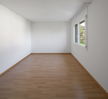 Empty room with parquet and window. White walls, perfect for copy-sace