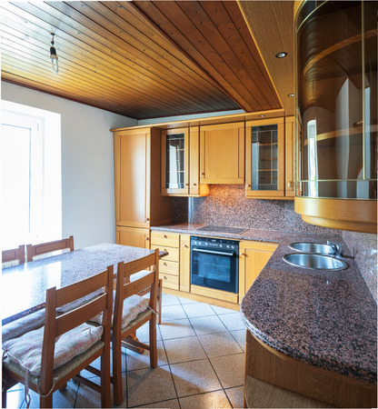 Kitchen with table and wooden furniture. Nobody inside. Standard-Bild - 103060351