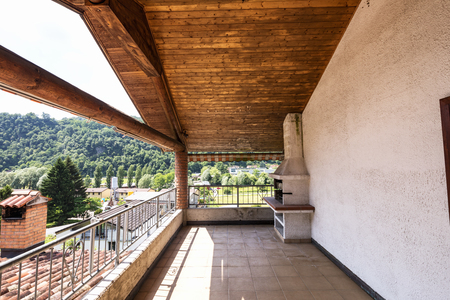 Terrace with wooden ceiling and tiles, landscape and hills. Nobody inside Standard-Bild - 103054253