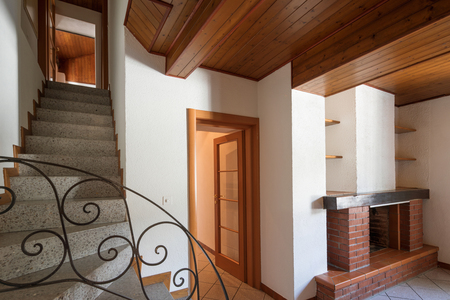Open door with granite stairs, another door and a fireplace. Nobody inside