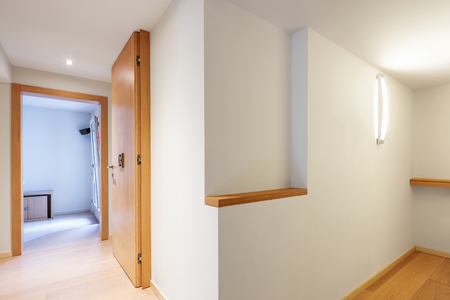 Fully white corridor with parquet in modern apartment. Nobody inside