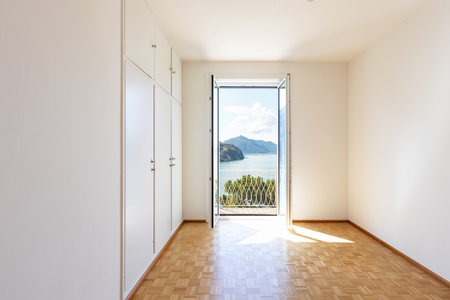 White room with large windows overlooking the lake. Nobody inside