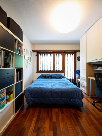 Front view bedroom with blue blankets, bookshelf and parquet. Nobody inside Stok Fotoğraf