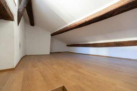 Attic with wooden beams and parquet. Nobody inside
