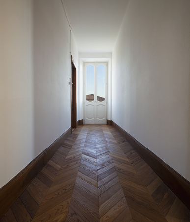 Corridor with antique wooden floor and window from which a lot of light enters. Nobody inside Standard-Bild - 114299888