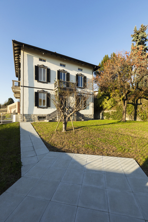 Exterior ancient villa with well-kept garden on a sunny day. Nobody inside Standard-Bild - 114299892