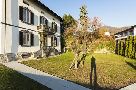 Exterior ancient villa with well-kept garden on a sunny day. Nobody inside Standard-Bild - 114299893