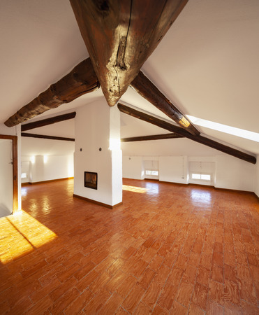 Attic with exposed wooden beams and a fireplace in the center of the room. Nobody inside Stock Photo