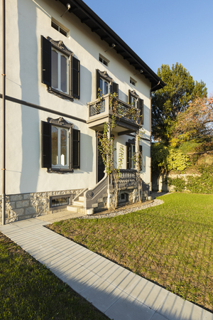 Exterior ancient villa with well-kept garden on a sunny day. Nobody inside Standard-Bild - 114299896