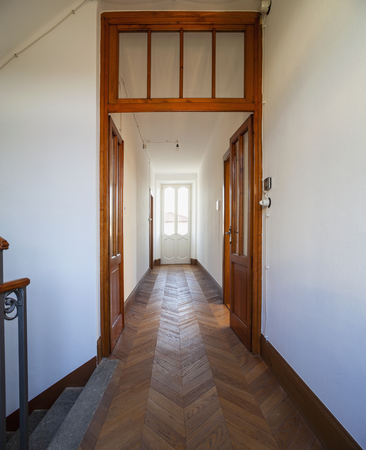 Corridor with antique wooden floor and window from which a lot of light enters. Nobody inside Standard-Bild - 114299899