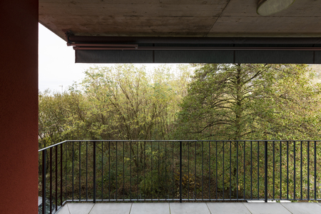 Terrace overlooking nature of apartment with red exterior walls. Nobody inside Standard-Bild - 114299933