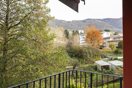Terrace overlooking nature of apartment with red exterior walls. Nobody inside Standard-Bild - 114299935