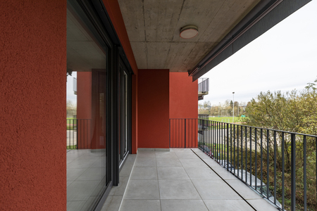 Terrace overlooking nature of apartment with red exterior walls. Nobody inside Standard-Bild - 114299937