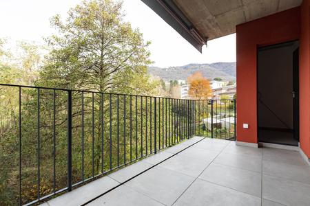 Terrace overlooking nature of apartment with red exterior walls. Nobody inside Standard-Bild - 114299944