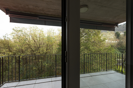 Terrace overlooking nature of apartment with red exterior walls. Nobody inside Standard-Bild - 114299976