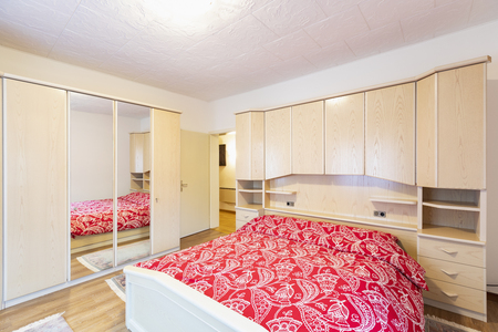 Bedroom with red blankets and wooden wardrobe. Nobody inside Standard-Bild - 114299981