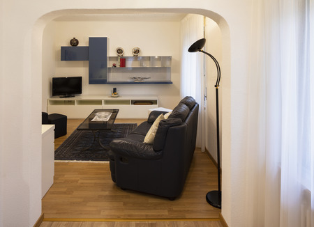 Living room with black leather sofa and parquet. Nobody inside Standard-Bild - 114299987