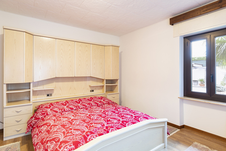 Bedroom with red blankets and wooden wardrobe. Nobody inside Standard-Bild - 114299990