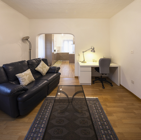 Living room with black leather sofa and parquet. Nobody inside Standard-Bild - 114300006