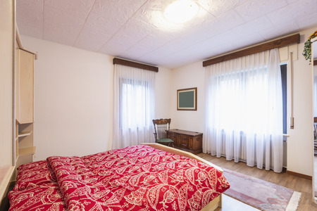 Bedroom with red blankets and wooden wardrobe. Nobody inside Standard-Bild - 114300007