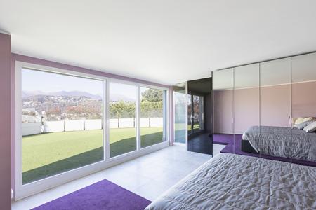 Bedroom overlooking the terrace with grass. Violet walls. Nobody inside Standard-Bild - 114300015