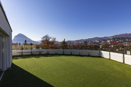 Terrace with synthetic lawn overlooking the city of Lugano in Switzerland. Nobody inside Standard-Bild - 114303375