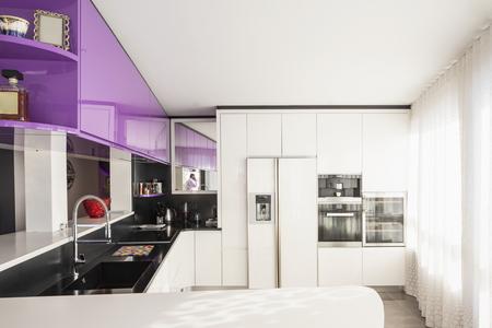 Kitchen with purple and white wardrobe, black counter. Elegant and minimalist. Nobody inside Standard-Bild - 114303376