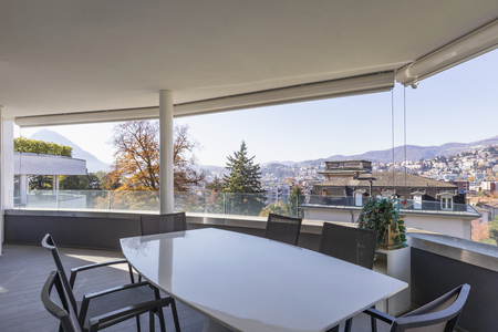 Lounge terrace composed of chairs and table overlooking the city of Lugano in Switzerland. Nobody inside Standard-Bild - 114303378
