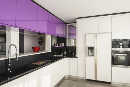 Kitchen with purple and white wardrobe, black counter. Elegant and minimalist. Nobody inside Standard-Bild - 114303380
