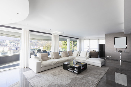 Living room with white leather sofa and windows overlooking the city of Lugano in Switzerland. Nobody inside Standard-Bild - 114303381