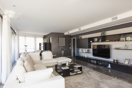 Living room with white leather sofa and windows overlooking the city of Lugano in Switzerland. Nobody inside Standard-Bild - 114303383
