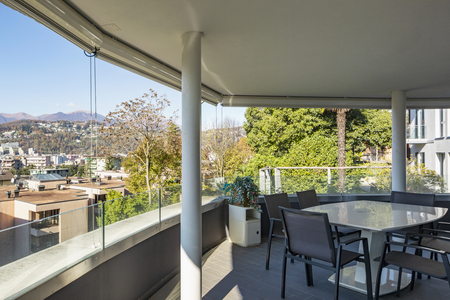 Lounge terrace composed of chairs and table overlooking the city of Lugano in Switzerland. Nobody inside Standard-Bild - 114303385