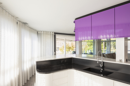 Kitchen with purple and white wardrobe, black counter. Elegant and minimalist. Nobody inside Standard-Bild - 114303387