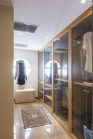Walk-in closet in wood and marble with large round lighted window. Nobody inside Standard-Bild - 114303392