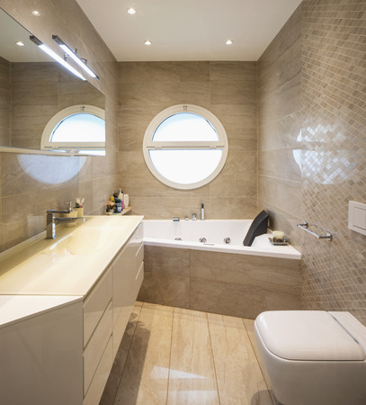 Elegant luxury bathroom with mosaic and circular window. Front view. Nobody inside 写真素材