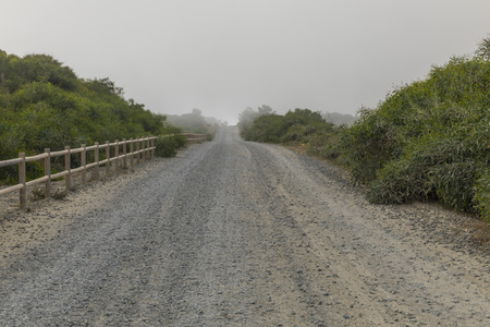 Dirt straight road, in the end fog. 写真素材