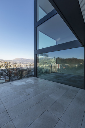 Modern glass palace terrace overlooking the city and Lake Lugano. Sunny day Standard-Bild