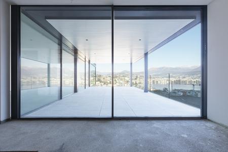Luxury apartment overlooking the city under construction. Nobody inside, concrete floor