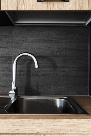 Stainless steel faucet detail of modern wooden kitchen. Nobody inside Stock Photo