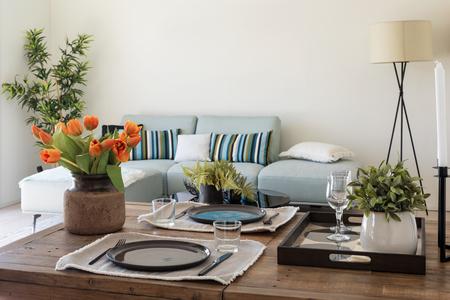 Particolare del tavolo in legno con piatti, posate e mazzo di tulipani arancioni. Soggiorno dal design moderno. Nessuno dentro