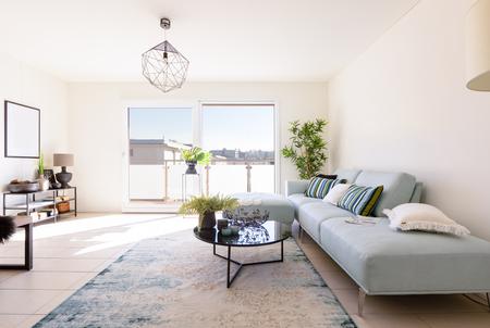 Modernes Wohnzimmer mit Designer-Sofa und Couchtisch. Fenster mit Aussicht. Niemand drin