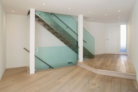 Entrance detail with modern glass staircase and parquet. Spotlights. Nobody inside Foto de archivo