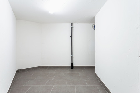 Cellar with gray tiles and white walls. Nobody inside Stock Photo