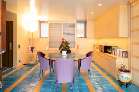Dining room with purple armchairs and blue tiles. No one inside