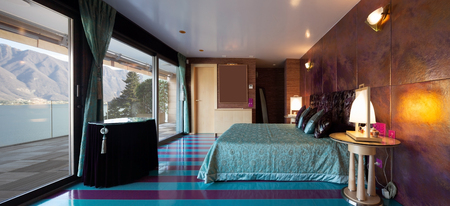 Luxurious bedroom with purple and blue stripes on the floor. No one inside