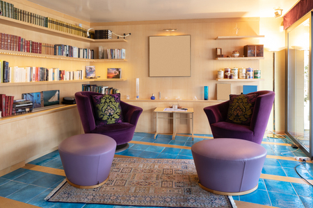 Living room with two large purple armchairs and wooden bookcase. No one inside
